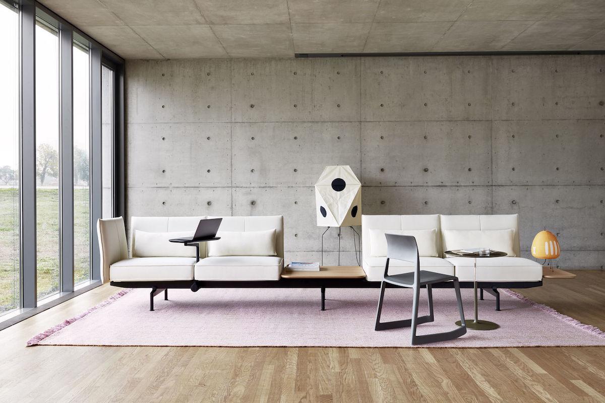 Raum mit kahlen Betonwänden und Decke. Soft Works Sitzmöbel in Creme, davor ein grauer Tip Ton Chair von Vitra