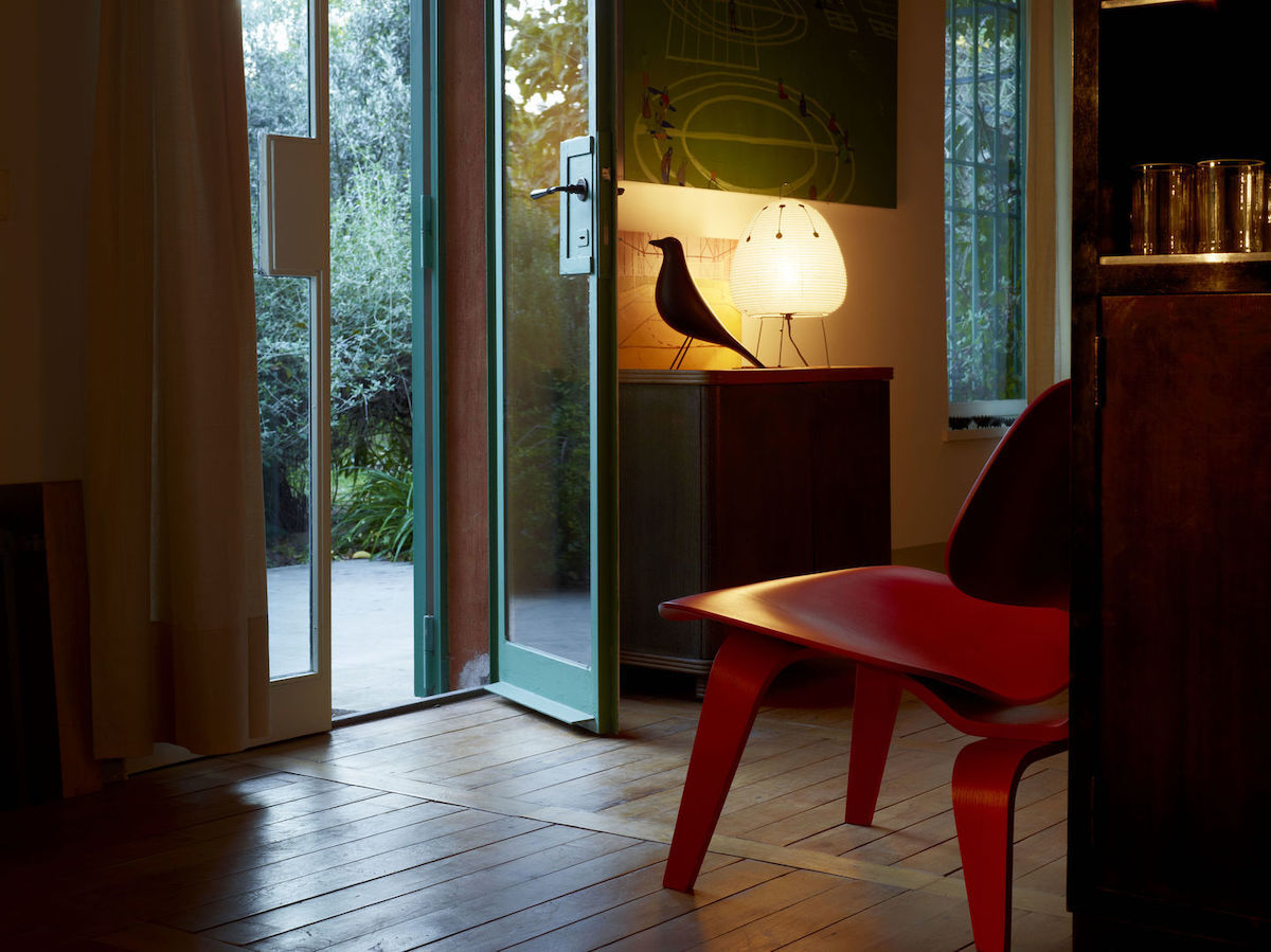 Blick aus einem Zimmer zur Terrassentür. Neben der Tür steht eine kleine Konsole, auf dieser eine Akari 1AD und ein Eames House Bird.