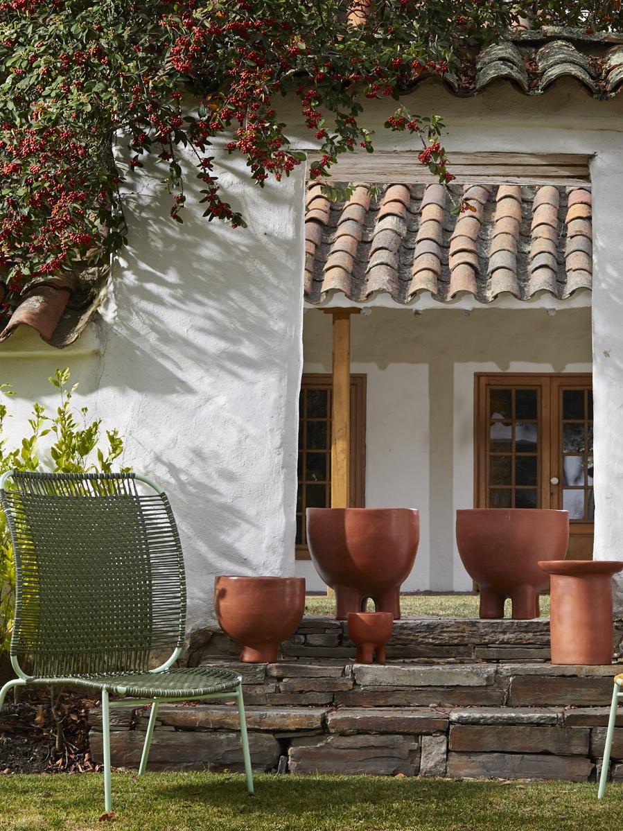 Gartenstufen. Auf denen stehen unterschiedlich große Gefäße aus der Ames Barro Kollektion in roter Tonerde. Links steht ein grüner Stuhl.