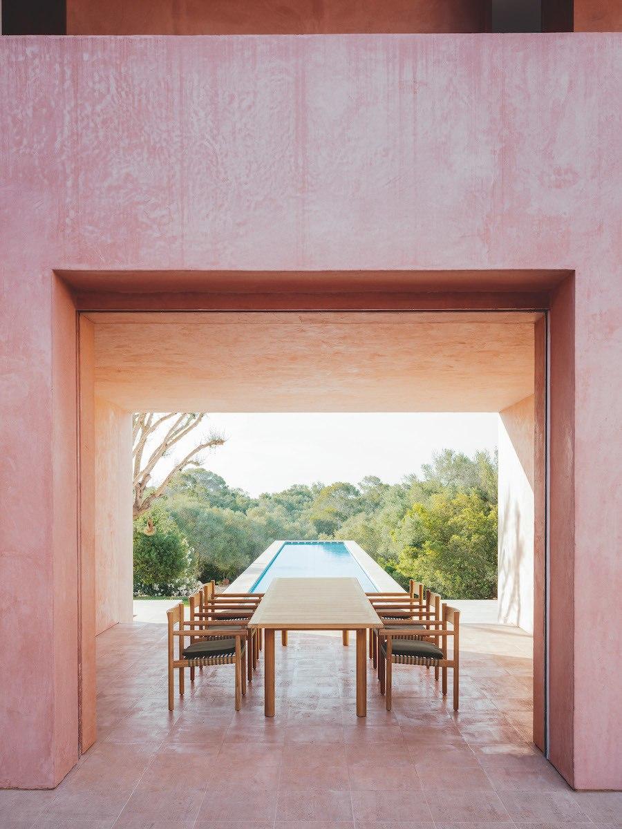 Tibbo Esstisch- und Stuhl Kombination auf einer rosa Terrasse mit ausrichtung zum Pool.