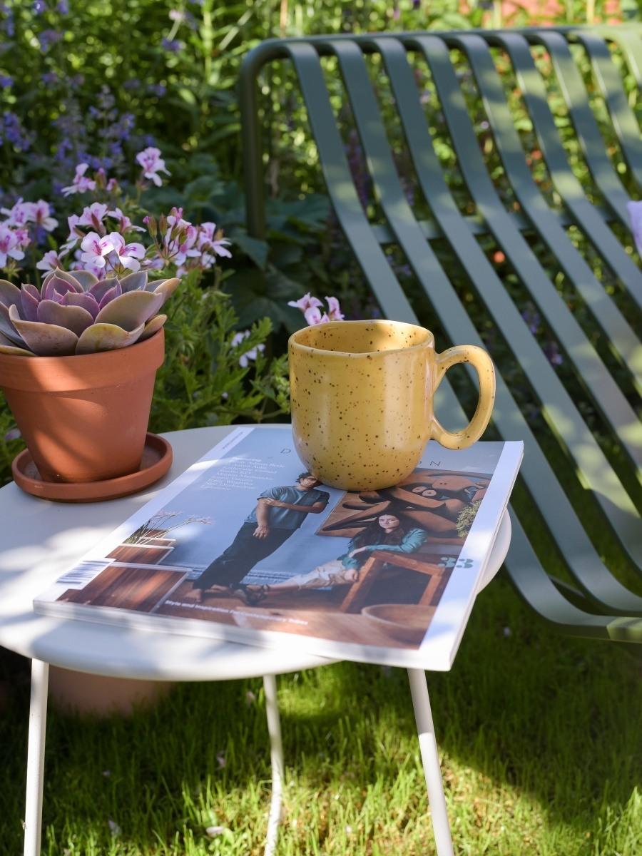 Vorn ein kleiner heller Beistelltisch mit Kaffeetasse, Magazin und Sukkulente im Terrakotta-Topf, im Hintergrund die grüne Palissade Sonnenliege.