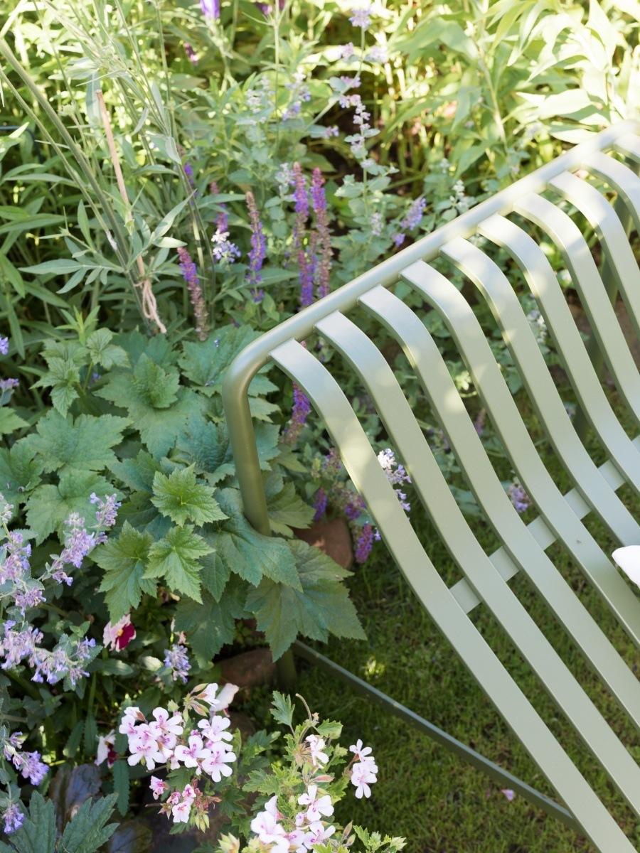 Blick auf Blüten und Blätter im Garten hinter der Rückenlehne einer Sonnenliege.