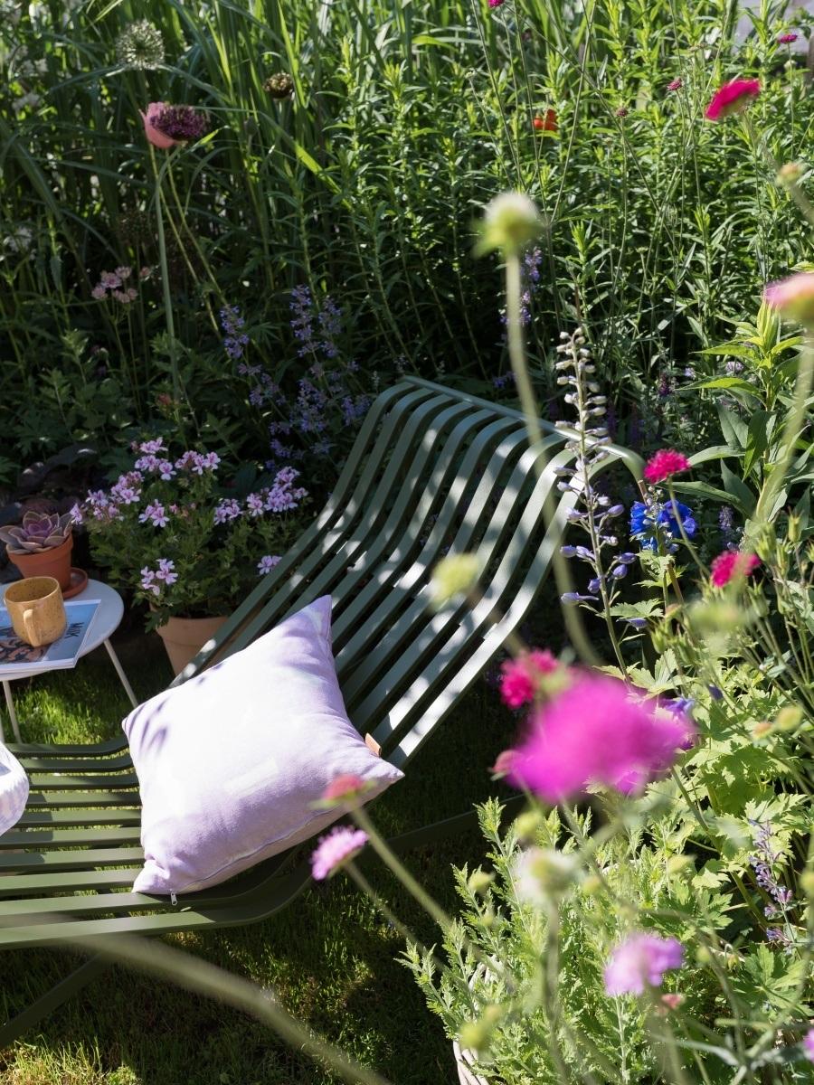 üppiger Sommerblumenwuchs, mitten drin steht eine Palissade Sonnenliege von HAY in grün.