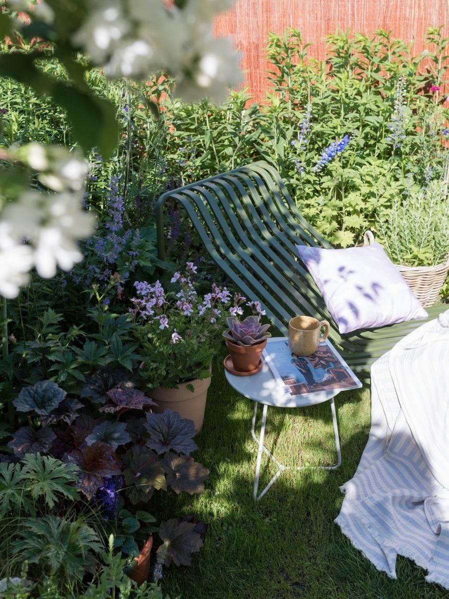 Ein neuer Lieblingsplatz im Garten -Blick auf die Sonnenliege. Darauf liegen ein Kissen und eine leichte Decke.