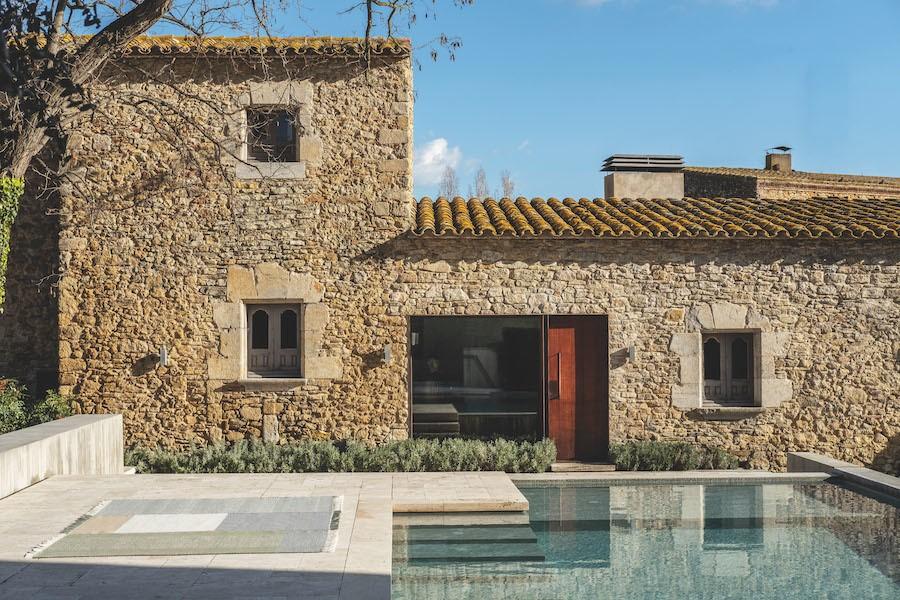Spanische Finca mit Pool. inks direkt neben dem Pool liegt ein Nanimarquina Tres Outdoorteppich in Farbmodell Salvia.